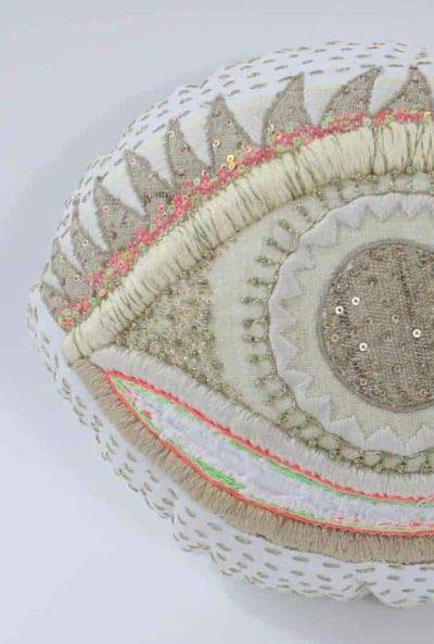 Fluor embroidery on an eye shaped cushion