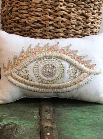 cushion filled with lavender with a multi coloured eye embroidered on it