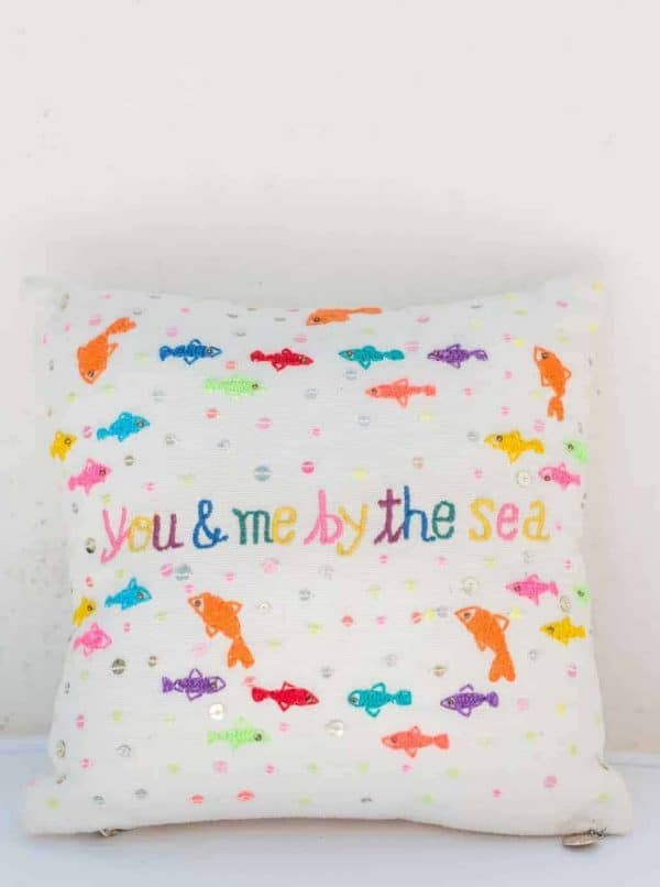 small square cushion with colourful embroidered fish on it that says you and me by the sea