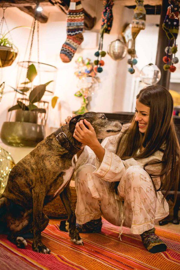 girl wearing cow print pyjamas cuddling a dog