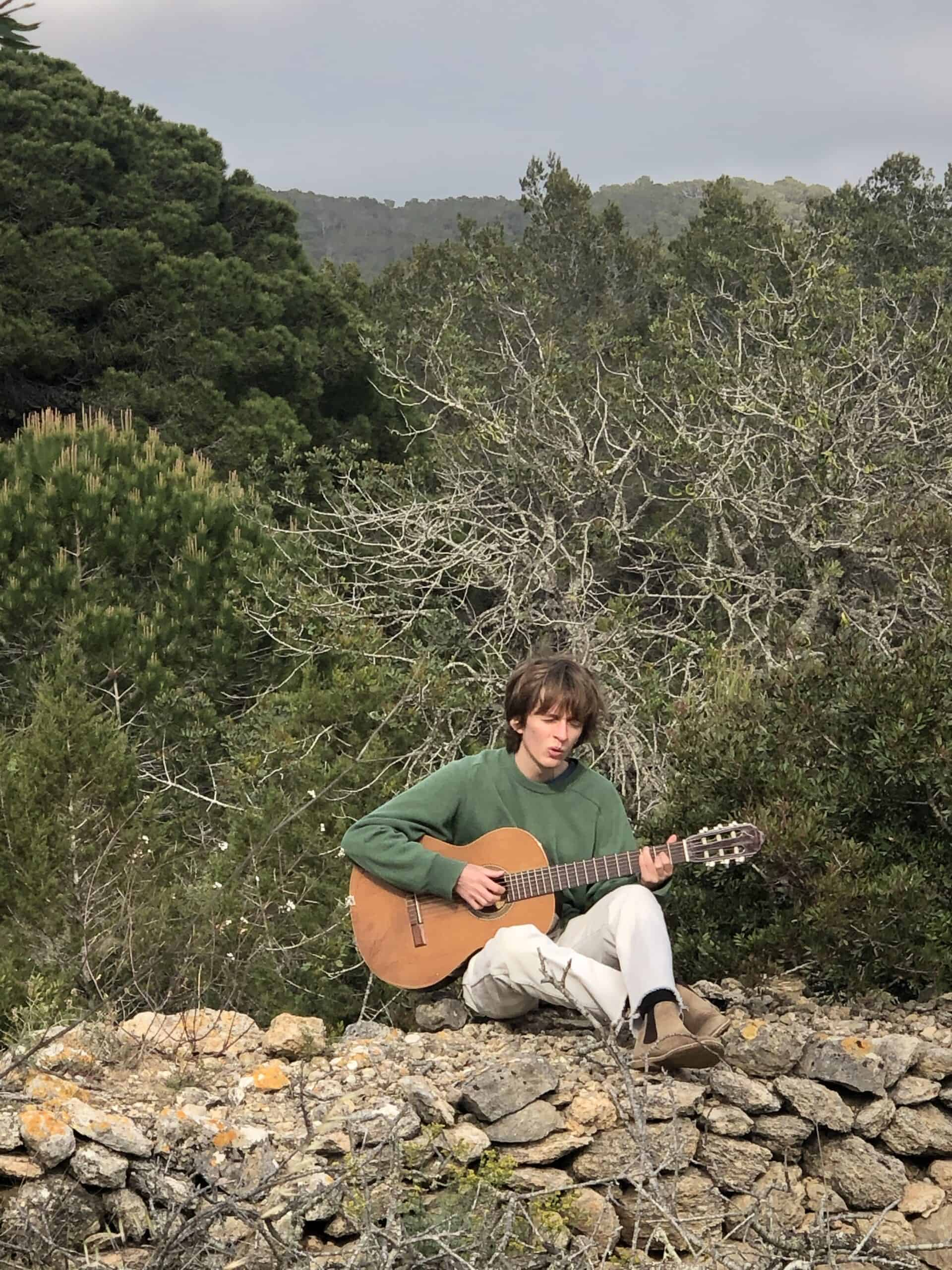playing guitar on a terraced wall