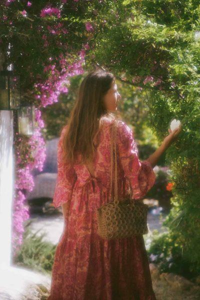 Girl in a pink dress walking through a garden