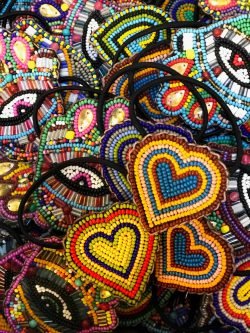 selection of beaded hair bobbles in the shape of hearts and hamsa hands