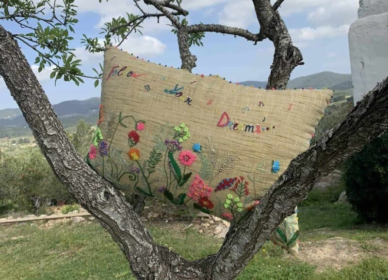 an embroidered cushion sitting in a tree