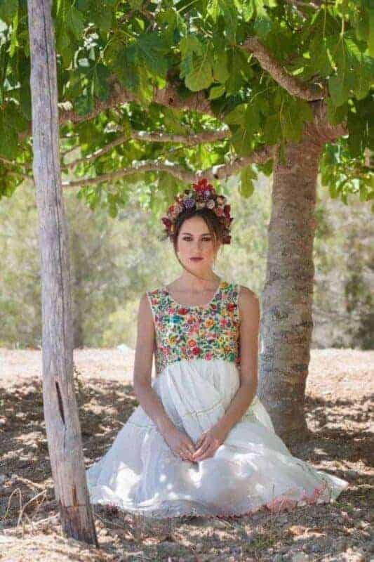girl kneeling between fig trees in a beautiful beaded dress