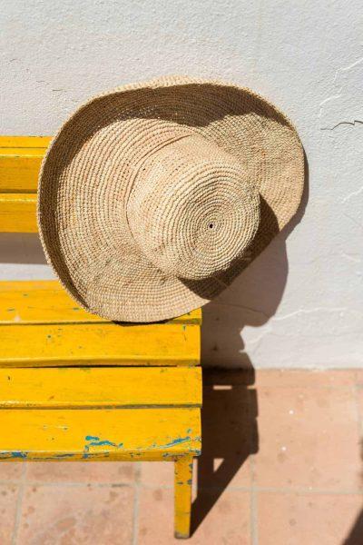 raffia hat on a yellow bench