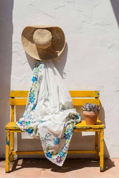 Raffia hat on a white wall with an embroidered shawl on a yellow bench