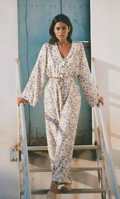 front view of a long sleeve jumpsuit in white with a yellow vine print