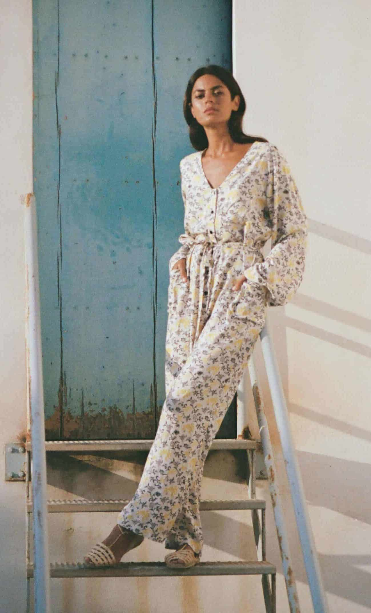 front view of a long sleeve jumpsuit in white with a yellow vine print side view