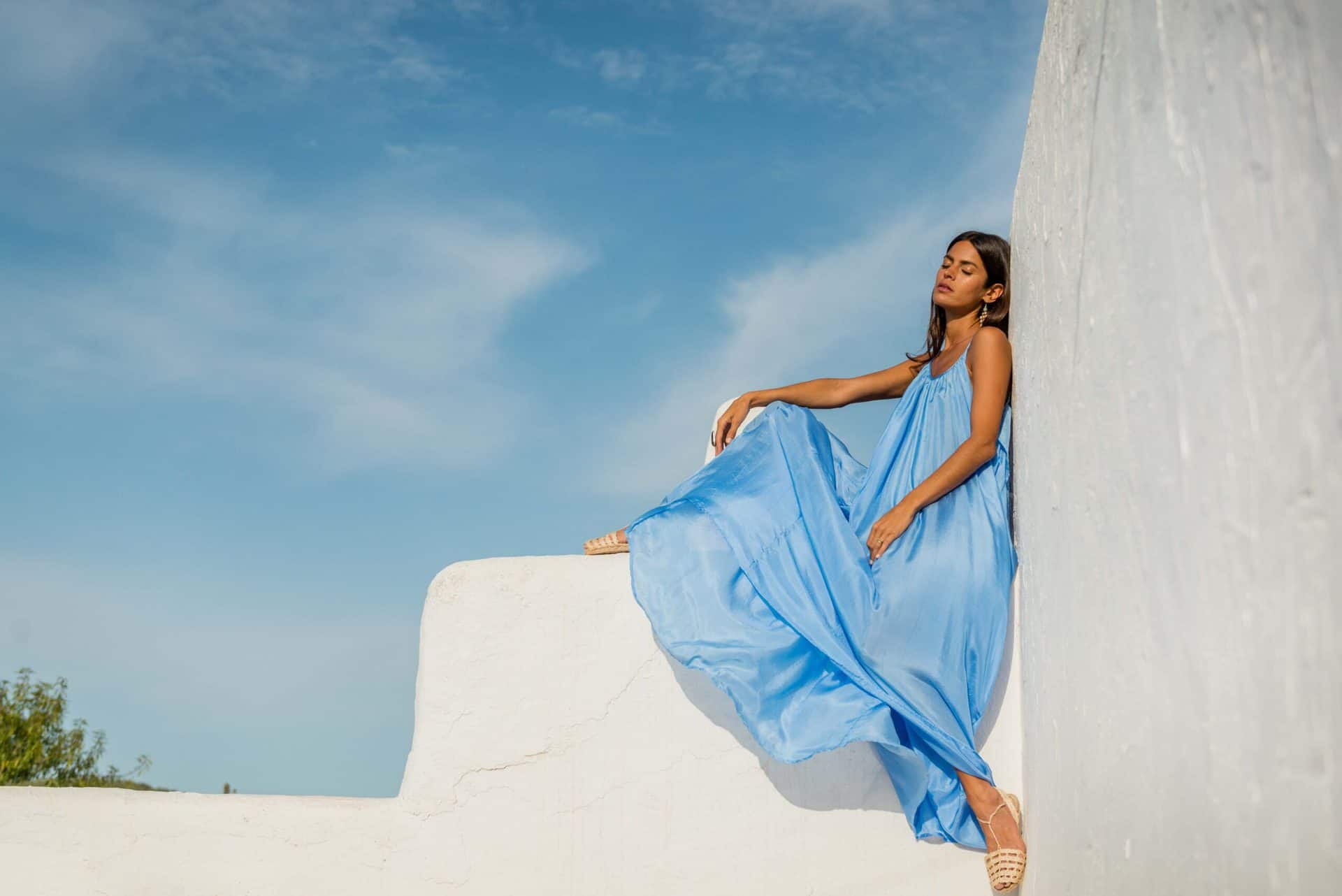 girl in a sky blue silk dress with a blue sky background