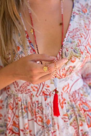 long beaded necklace with red tassel