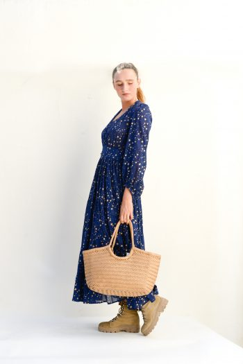 navy long sleeved dress with gold stars and a leather basket