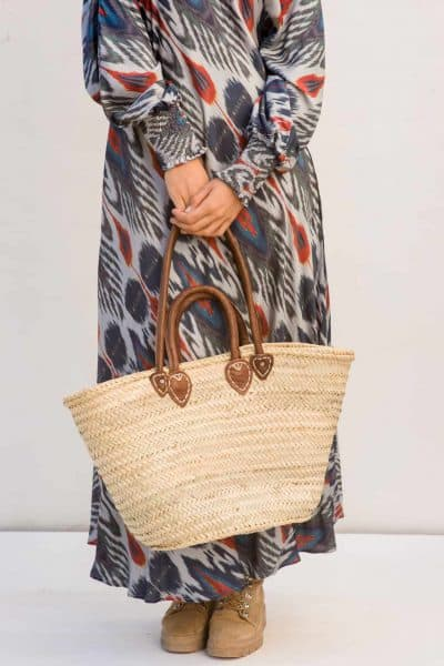 ibiza style basket with brown leather handles and a long bohemian dress