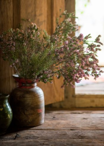 wooden vase filled with pink heather branches