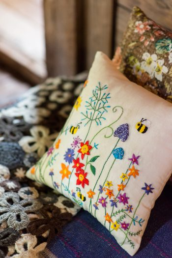 white cushion with an embroidered garden