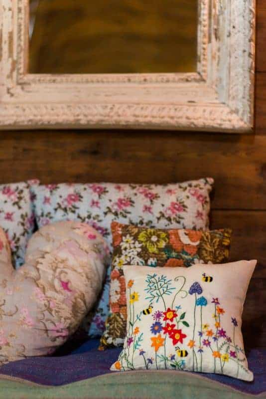 square cushion with colourful floral embroidery and bees