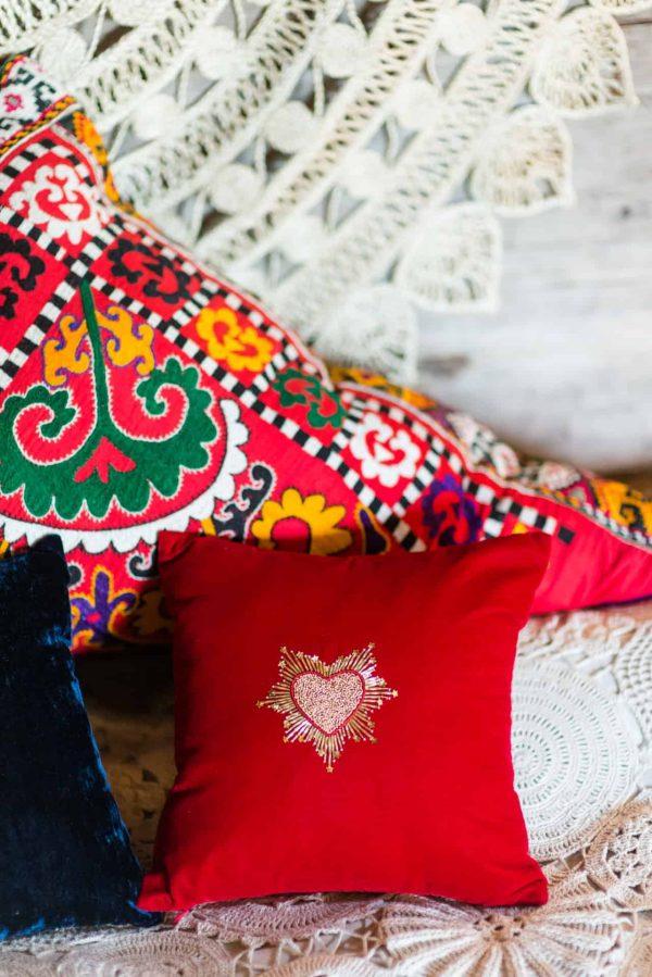 beaded heart on a red velvet cushion