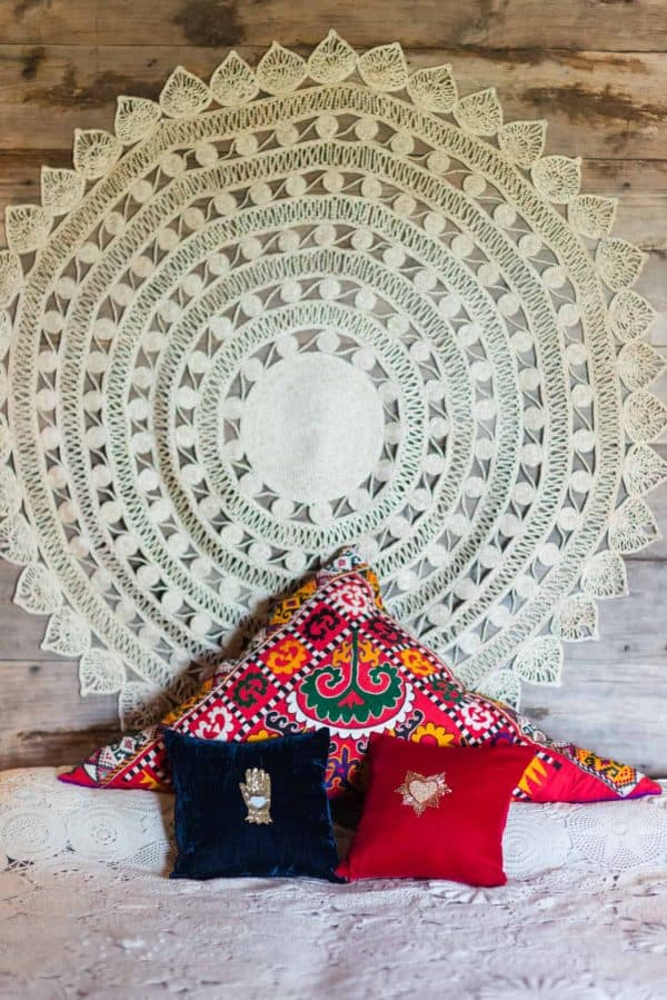 round jute wall hanging above a bed with cushions