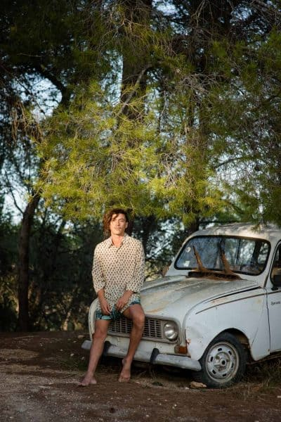 Modelling hand block print shirts and shorts sitting on a Renault 4 car