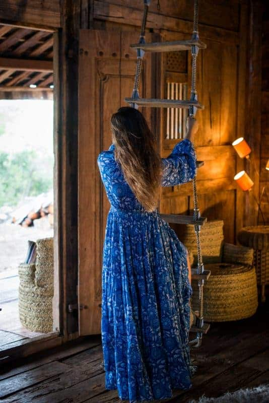 swinging on a rope ladder in a blue and white maxi dress