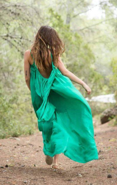 Skipping through a forest in a green silk dress