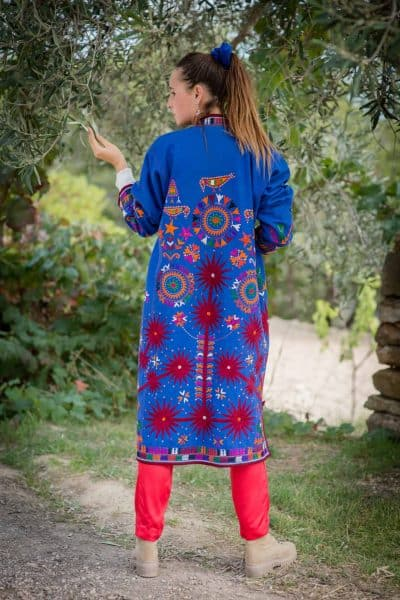 long blue woollen coat with colourful bird embroidery and red suns