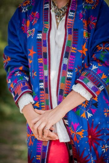 multicoloured embroidery on a blue wool coat