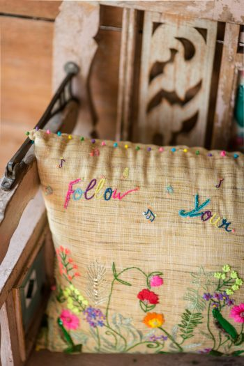 Close up of a cushion with floral embroidery and multicoloured French Knotting along the edge