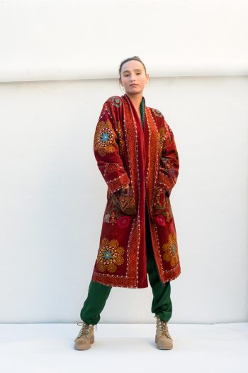 long rust coloured coat with embroidery and green trousers