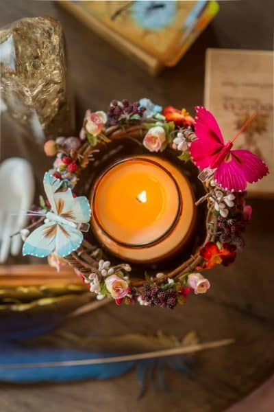 Candle in a wicker basket with butterflies and flowers