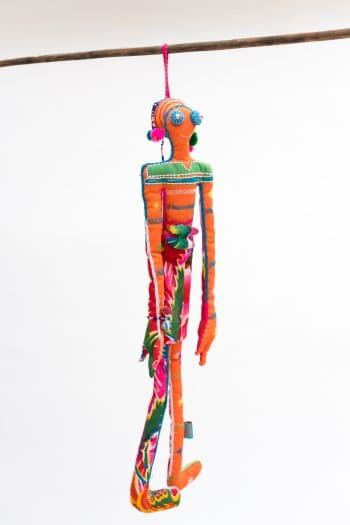 cloth doll with long arms and legs and beaded detail