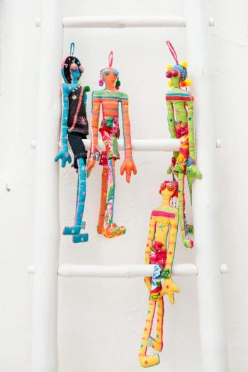 Colourful stuffed dolls perched on a ladder