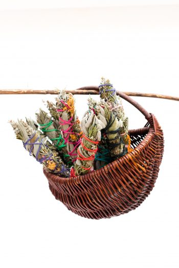 Basket of herb smudge sticks with crystals