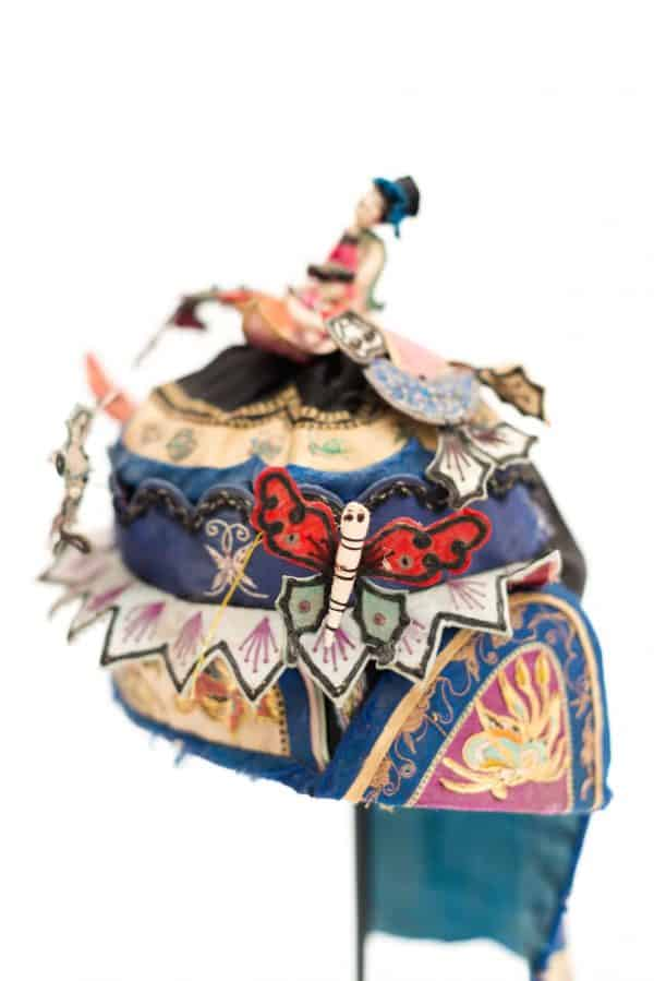 needlework detail on a blue Chinese headdress
