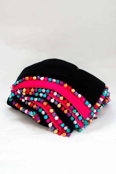 multicoloured silk ball trim on a black velvet blanket with pink lining