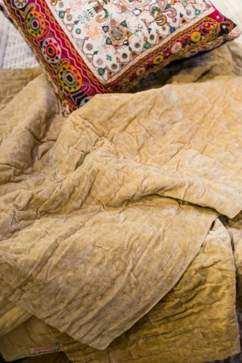sandy coloured velvet bedspread with embroidered cushion