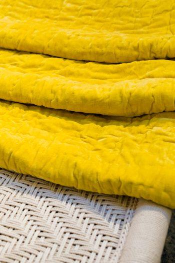 folded yellow velvet bedspread on a macrame bed