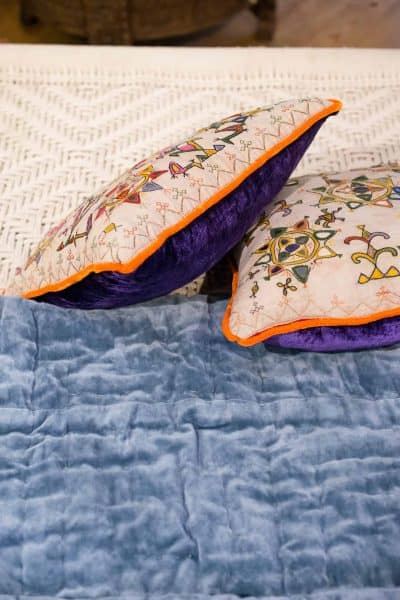 Blue velvet, embroidered cushions & macrame bed
