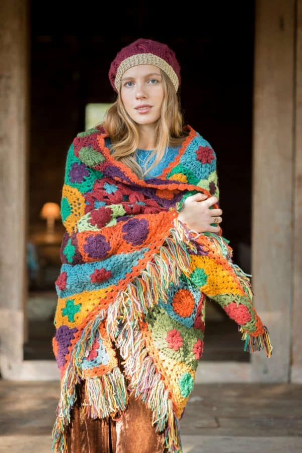 multicoloured crochet shawl in the shape of a triangle worn with a burgundy beanie hat