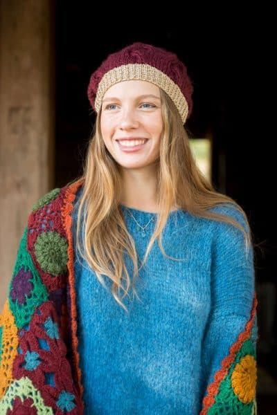 blue mohair jumper worn with a burgundy beanie hat with a gold rim