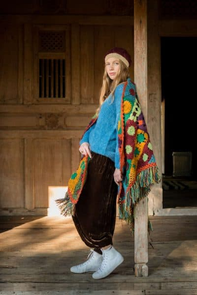 multicoloured crochet triangle shawl with blue jumper and brown velvet trousers