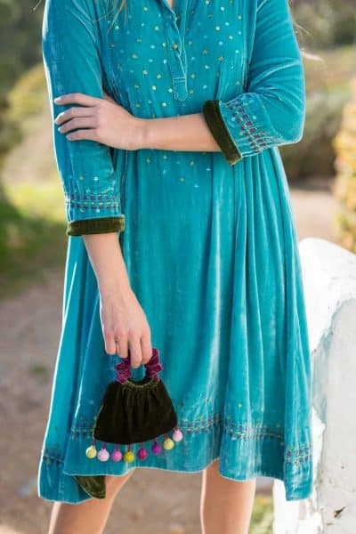 close up of a turquoise velvet dress with contrasting green hems and a running kantha stitch