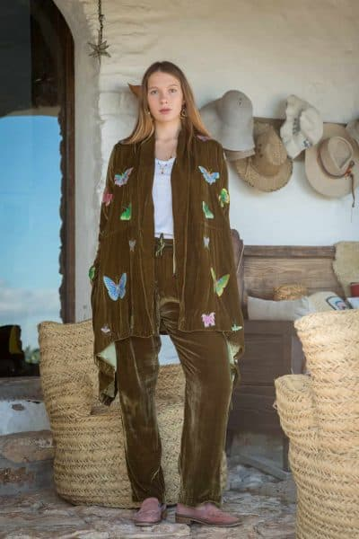 colourful butterfly embroidery on a silk velvet jacket worn with matching trousers