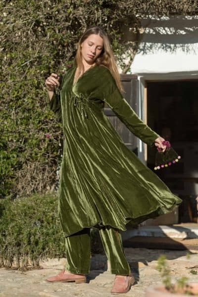 twirling in a long green velvet coat holding a green velvet bag