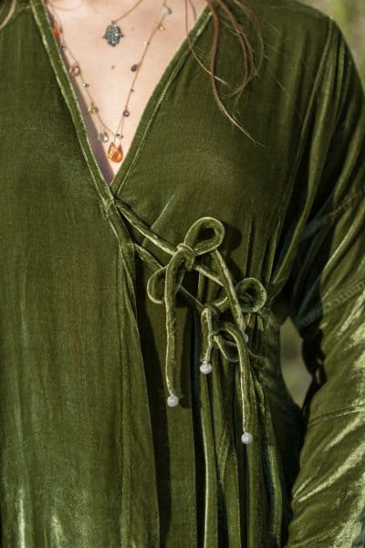 close up view of the tie on a green velvet coat