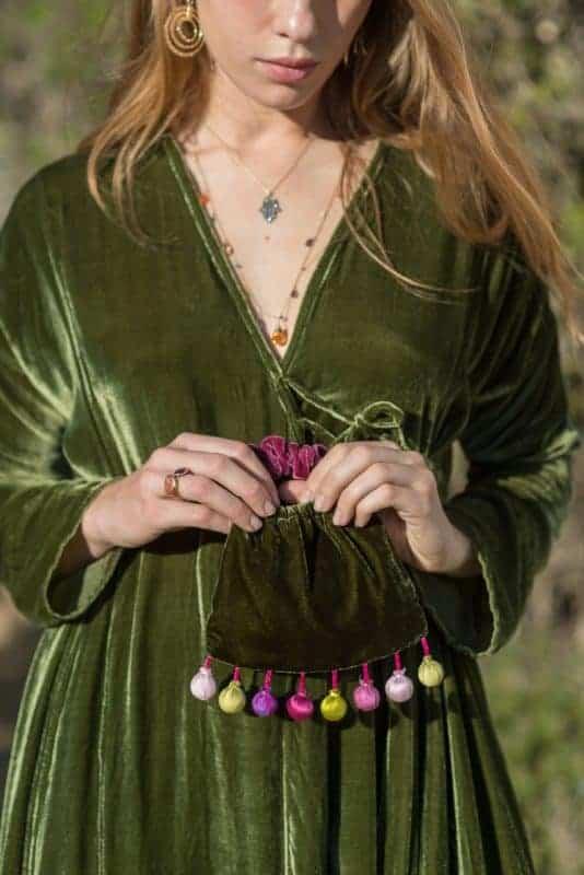 green velvet bag with a purple velvet handle and silk balls