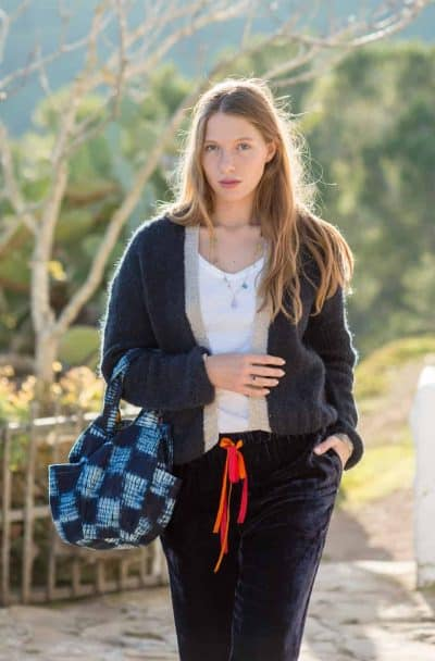 velvet trousers worn with a wool cardigan and a blue pumpkin shaped bag