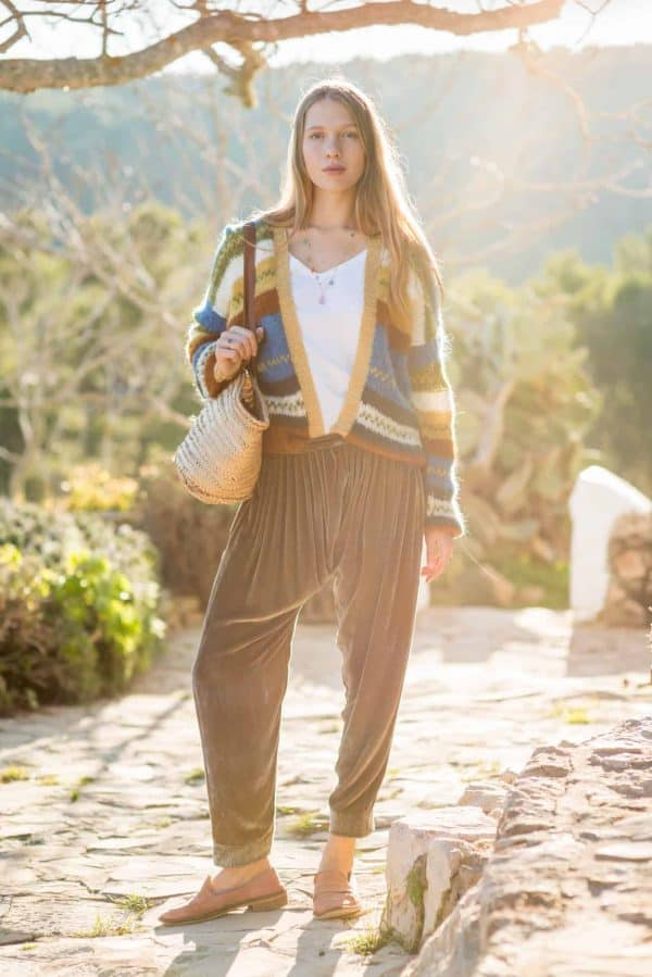 olive green trousers worn with a colourful striped cardigan