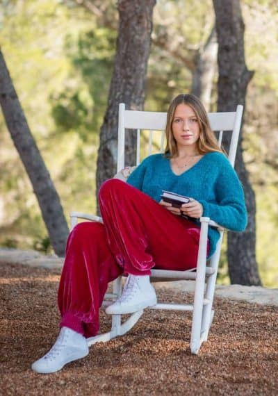 sitting in a rocking chair wearing pink velvet trousers and a blue alpaca wool jumper