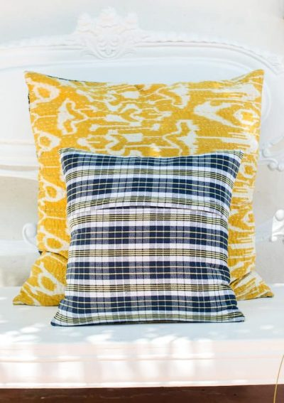 Back and front view of a yellow ikat print cushion with kantha stitch